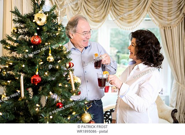 Senior couple drinking punch by Christmas tree