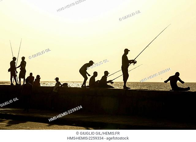 Cuba, Havana, Malecon, Habana Vieja district listed as World Heritage by UNESCO, fishermen at evening time