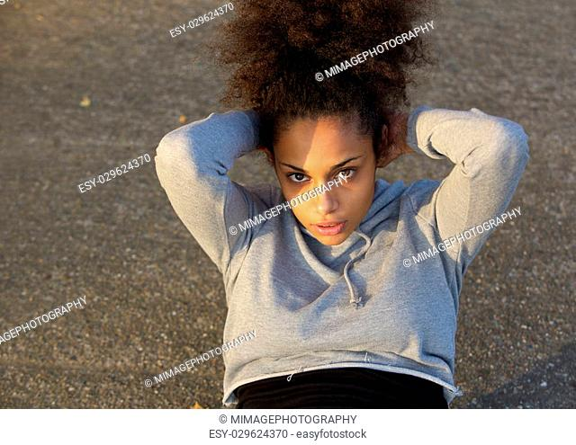 Young african american woman doing sit ups outdoors