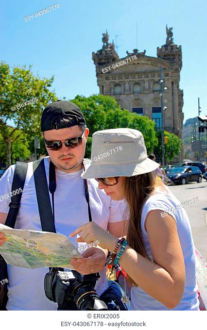 Tourists looking at a city map in La Rambla Street in the center of Barcelona, Spain. It is one of the most famous street and promenade among tourists