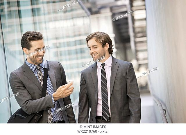 Two men in business suits outside a large building, one holding a smart phone