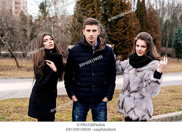Three beautiful people in the autumn park