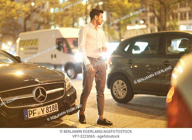young man walking on street at night, cars, traffic, city, fashionable, in Munich, Germany