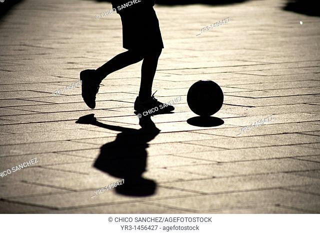 A boy plays soccer in the main square of Merida, Badajoz province, Extremadura region