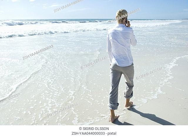 Barefoot businesswoman walking through surf on beach, using cell phone