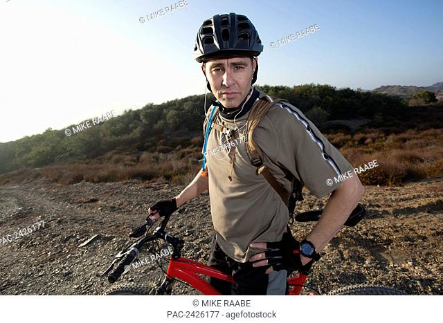 A man posing with his mountain bike and helmet