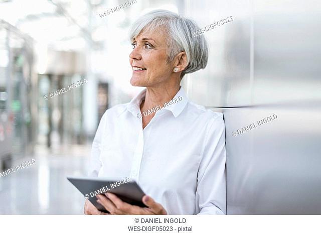 Portrait of smiling senior businesswoman holding tablet