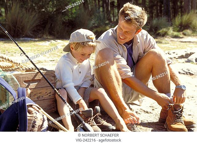 outdoor, blond 6-year-old boy and his father squad in a forest removing their walking boots  - GERMANY, 19/09/2004