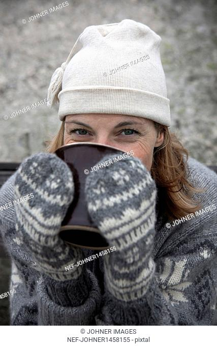 Portrait of woman wearing warm clothing drinking hot drink