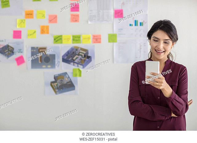 Happy businesswoman in office looking at cell phone
