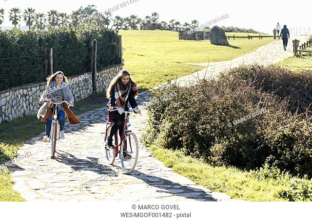 Two young women riding bicycle along a path