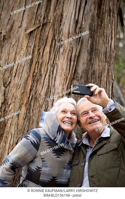 Older couple taking photographs together in park