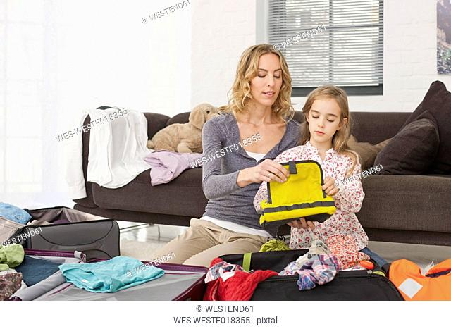 Germany, Leipzig, Mother and daughter packing suitcase for vacation