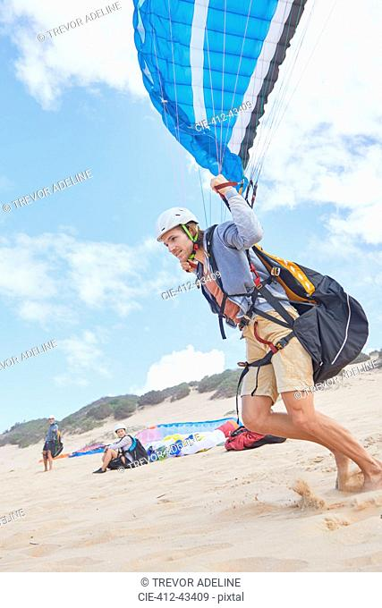 Male paraglider running on beach