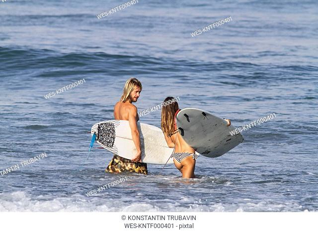 Indonesia, Bali, Surfer couple going into water
