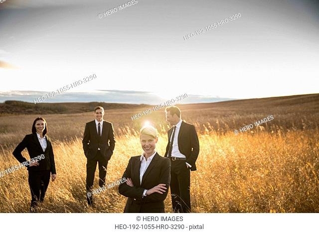 Portrait of smiling business people on field