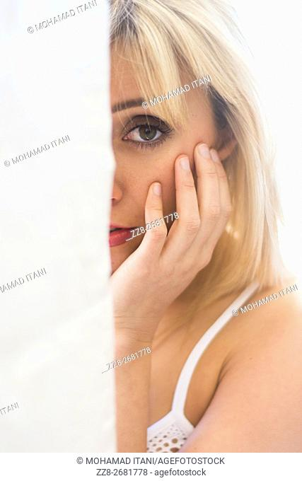 Young woman hiding behind a wall