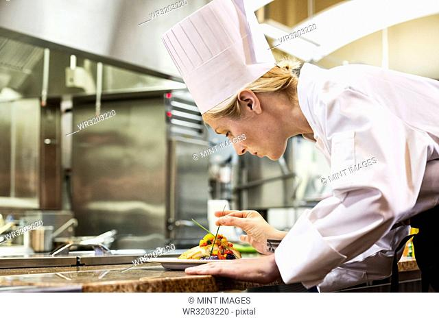 A Caucasian female chef putting the finishing touches on a plate of fish in a commercial kitchen