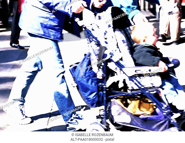 Woman pushing a stroller, view from waist down