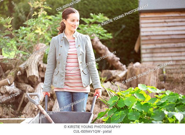Female gardener pushing wheelbarrow in rustic organic garden