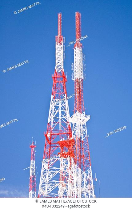 Colorful radio, microwave and cell towers against a pure blue sky
