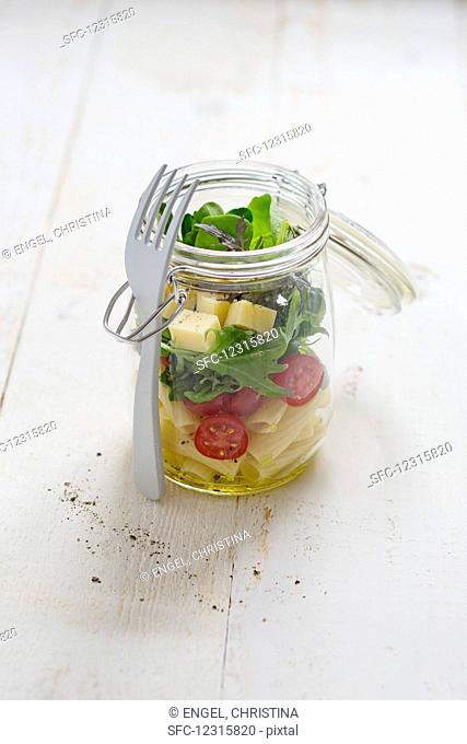 A pasta salad with cocktail tomatoes, rocket and mountain cheese in a glass jar with a fork
