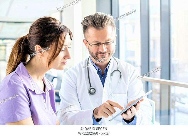 Doctor and nurse looking at digital tablet in hospital