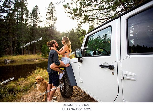 Romantic young couple next to jeep on riverside, Lake Tahoe, Nevada, USA