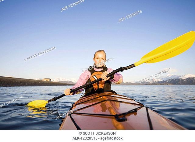 Young woman sea kayaking in Kachemak Bay, near Homer, South-central Alaska; Alaska, United States of America