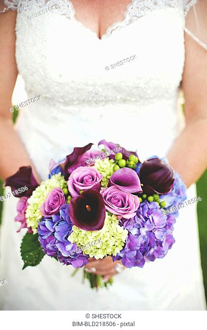 Close up of bride holding wedding bouquet