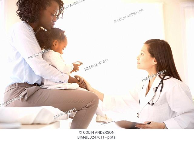 Crouching Doctor comforting woman and daughter