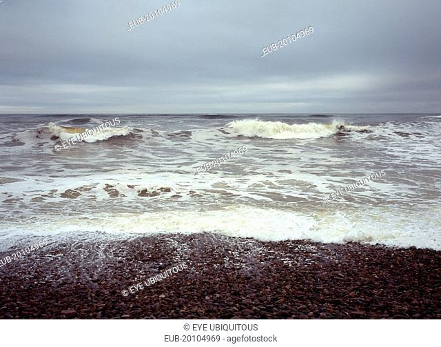 North facing shingle beach looking out across rough sea and surf