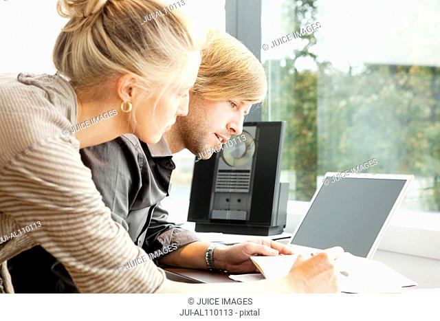 Mid adult couple working together at desk at home