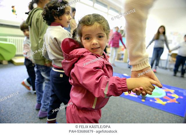Alma from Syria, an asylum-seeker, in a circle with other children during a Birthday celebration at the initial processing center for refugees in Messstetten