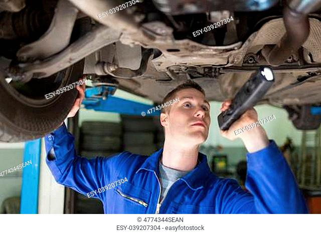 Male mechanic with frashligth examining under car