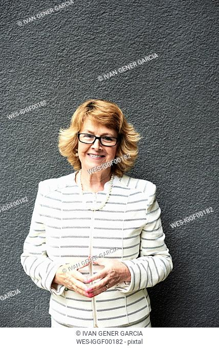 Portrait of smiling senior businesswoman against grey wall