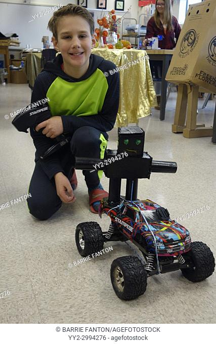 6th Grade Boy Showing Off Robot and Remote Controlled Car, Wellsville, New York, USA