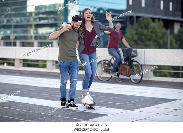 Young man supporting laughing girlfriend on skateboard