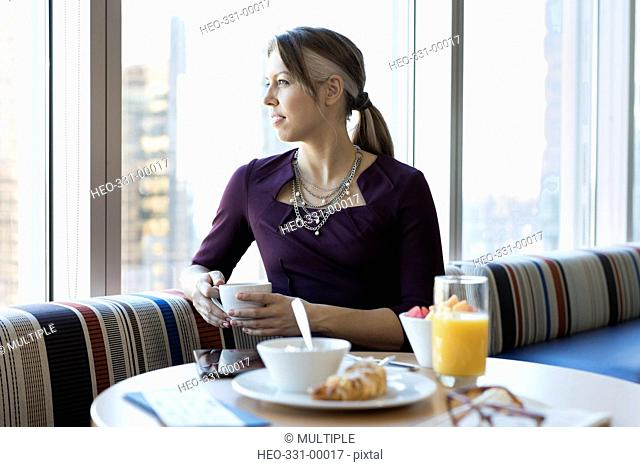 Pensive businesswoman looking out window and drinking coffee at breakfast in lounge