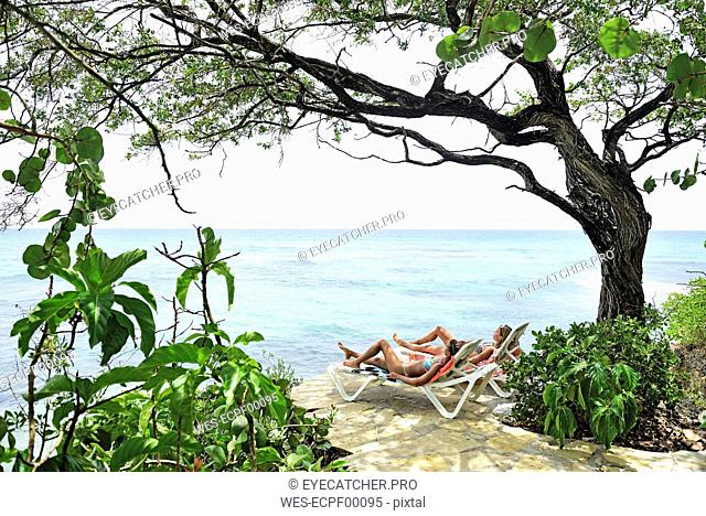 Two women relaxing on sun loungers at the sea