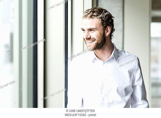 Smiling young businessman looking out of window in office