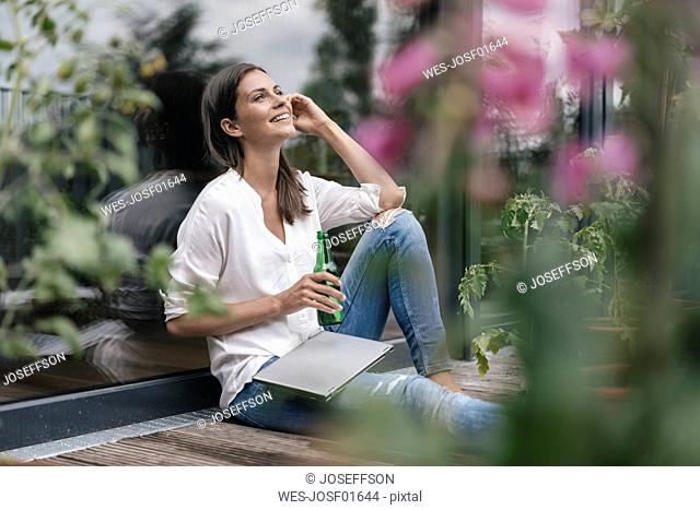 Happy woman with laptop and bottle sitting on balcony