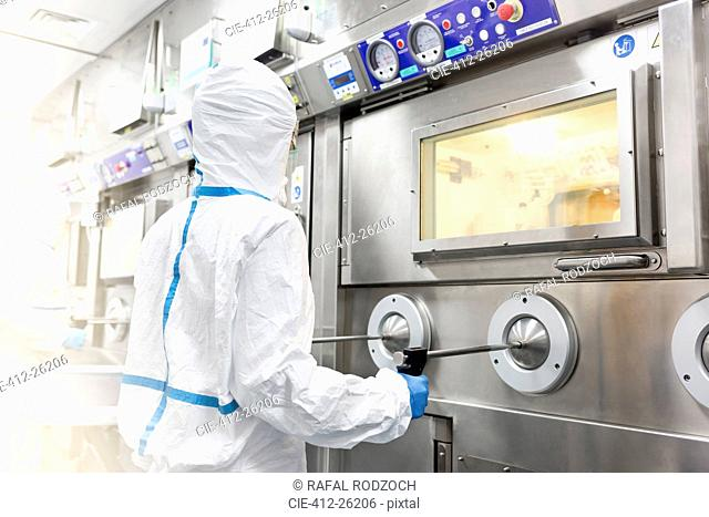 Scientist in clean suit operating machinery in laboratory