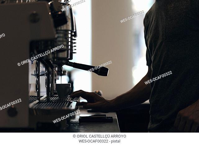Barista preparing coffee in a coffee bar, partial view