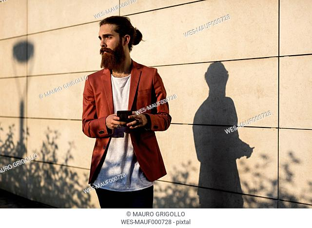 Fashionable young man with smartphone looking at distance
