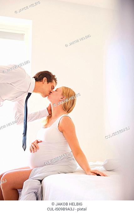 Pregnant woman kissing businessman husband in bedroom