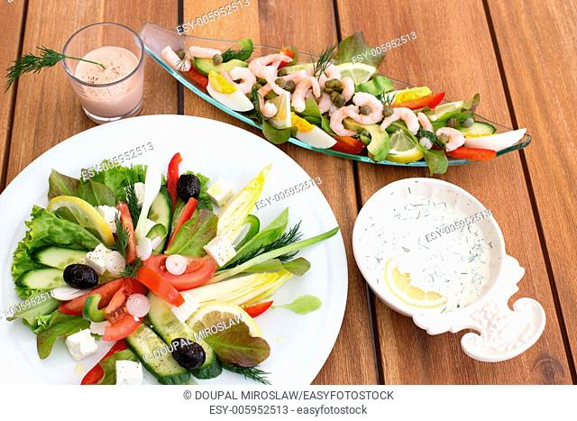 Composition of greek salad and shrimp cocktail on a wooden table