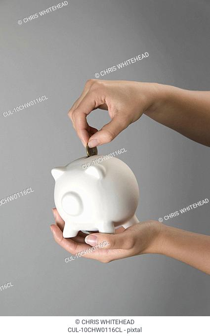 Female hand placing coin in piggy bank