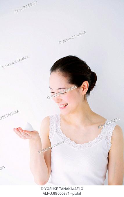 Young woman with face-wash foam