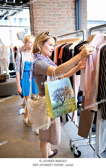 Mature woman looking at clothes in shop